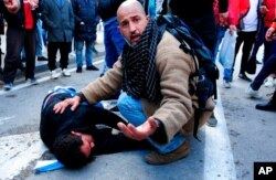 A demonstrator takes care of a man wounded by police during a protest in Tunis, Jan. 23, 2021. Tunisia is extending its virus curfew and banning demonstrations as it tries to stem a rapid rise in infections and calm tensions from protests.