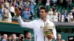 Serbia's Novak Djokovic holds the trophy after defeating Switzerland's Roger Federer in the men's singles final match of the Wimbledon Tennis Championships in London, July 14, 2019.