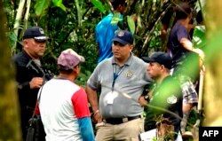 Police and employees of the Public Ministry investigate near a mass grave with seven bodies at the indigenous region of Ngabe Bugle, Panama, Jan. 15, 2020, in this screen grab taken from Panamanian channel TVN Noticias.