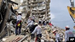 In this image, released by the Miami-Dade Fire Department, rescuers search for survivors in the rubble of the Champlain Towers South building in Surfside, Florida, on June 25, 2021.