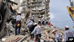 Imagem disponibilizada pelo Departamento de Bombeiros de Miami-Dade, em que equipas de resgate procuram por sobreviventes nos escombros do edifício sul das Torres Champlain, em Surfside, Florida, 25 Junho, 2021.