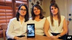 Dennysse Vadell (tengah), istri eksekutif perminyakan Tomeu Vadell yang ditahan di Venezuela, didampingi kedua putrinya, menunjukkan foto suaminya, di Katy, Texas, 15 Februari 2019.