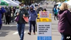 Potrošači s maskama na pijaci u zapadnom Sijetlu , koja se proteklog vikenda otvorila prvi put u poslednja dva meseca (Foto: AP)