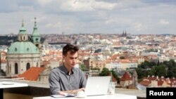 FILE - Joseph Petrila, a 23-year-old job seeker, uses a laptop in a cafe near the Prague Castle following the coronavirus outbreak, in Prague, Czech Republic, July 8, 2020.