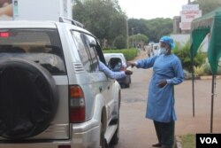 A health official disinfects people arriving at Wilkins Hospital, in Harare, May 12, 2021. (Columbus Mavhunga/VOA)