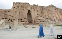 FILE - Two women walk past the cliffs that once held giant Buddhas destroyed by the Taliban in 2001 in Bamiyan, central Afghanistan, June 17, 2009.