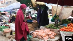 A woman buys vegetables from a local vendor in the Eastleigh neighborhood of Nairobi. The neighborhood is under lockdown after a spike in COVID-19 cases. (Mohammed Yusuf/VOA)
