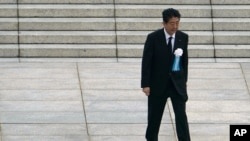 FILE - Japanese Prime Minister Shinzo Abe walks off after delivering a speech during a ceremony to mark the 75th anniversary of the bombing at the Hiroshima Peace Memorial Park, in Hiroshima, Aug. 6, 2020.