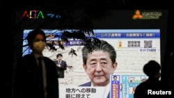 A pedestrian wearing a protective mask walks past a large screen on a building showing Japan's Prime Minister Shinzo Abe declaring a state of emergency, following the coronavirus disease (COVID-19) outbreak, in Tokyo, Japan April 7, 2020. REUTERS…