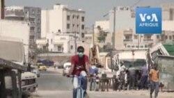 Un étudiant sénégalais rattache du désinfectant à son vélo