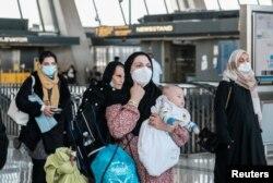 阿富汗难民抵达华盛顿附近的杜勒斯国际机场后登上接送他们前往受理中心的巴士。(2021年8月28日)