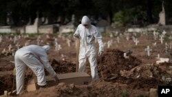 Brezilya'nın başkenti Rio de Janeiro'da görevliler koruyucu kıyafetler içerisinde Corona virüsü salgını nedeniyle hayatını kaybedenleri defnediyorlar.