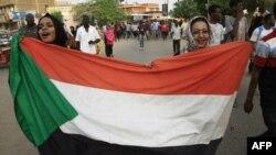 蘇丹婦女2019年6月30日在首都喀土穆的集會上舉著國旗遊行。