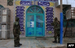 FILE - Soldiers disinfect the exterior of a mosque as a preventive measure against the spread of the coronavirus COVID-19, in the Shi'ite shrine city of Karbala, south of Iraq's capital Baghdad, March 7, 2020.