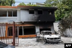 A charred car and building are pictured near the Petionville police station, where suspects in the assassination of President Jovenel Moise are being held, in Petionville, Haiti, July 9, 2021.