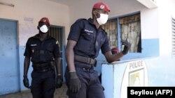 Des policiers portent des masques au marché aux poissons de Pikine à Dakar, au Sénégal, le 24 mars 2020. (Photo by Seyllou / AFP)