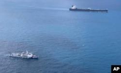 Dalam foto tak bertanggal yang dirilis oleh Badan Keamanan Laut Indonesia (BAKAMLA), sebuah kapal BAKAMLA mengawal kapal tanker MT Horse berbendera Iran (kanan atas) saat berlayar menuju Pulau Batam, Indonesia. (Bakamla via AP)