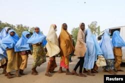 FILE - Girls who were kidnapped from a boarding school in the northwest Nigerian state of Zamfara walk in line after their release, in Zamfara, Nigeria, March 2, 2021.
