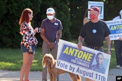 Kandidat Demokrat untuk Distrik Kelima Kongres, Antone Melton-Meaux (tengah) berbincang dengan penduduk di selatan Minneapolis, pada Hari Pemilihan Pendahuluan di Minnesota, Selasa, 11 Agustus 2020. (Foto AP / Jim Mone)