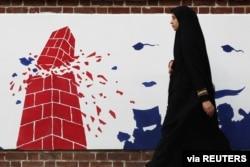 FILE - A woman walks past an anti-U.S. mural on the former U.S. Embassy's wall in Tehran, Iran, Jan. 7, 2020.