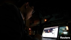 FILE - A Vietnamese internet activist posts a status on Facebook at a cafe in Hanoi, Nov. 27, 2013.