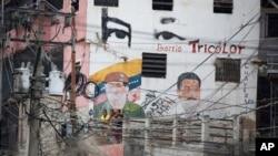 Cables de electricidad cuelgan frente a un edificio con las imágenes borrosas del difunto presidente venezolano Hugo Chávez, a la izquierda, y del actual presidente Nicolás Maduro en el barrio de Petare, en Caracas.