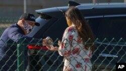 13일 미국 로스앤젤레스 공항에서 차량 공유 서비스 '우버' 운전자가 승객에게 손 소독제를 제공하고 있다.