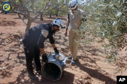 FILE - Syrian Civil Defense group inspects cluster bombs in the Khan Sheikhoun neighborhood of Idlib, Syria, Sept. 29, 2016.