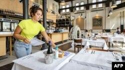 Seorang pekerja restoran menyiapkan meja-meja saat pembukaan kembali bisnis di Amsterdam, Belanda, Selasa (26/5).