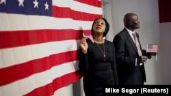Dvoje novih američkih državljana pozira ispred američke zastave posle polaganja testa za državljanstvo na Menhetnu u Njujorku, 13. septembra 2015.
