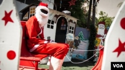 Abdou Khadre Diop, dressed as Santa Claus, waits for children to visit at Patisseries des Ambassades in Dakar, Senegal, Dec. 19, 2019. (Annika Hammerschlag/VOA)