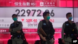 Riot police wearing face masks stand guard in front of a bank electronic board showing the Hong Kong share index at Hong Kong Stock Exchange, May 28, 2020.