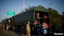 Migrantes venezolanos se suben a camiones militares para viajar gratis desde el servicio fronterizo ecuatoriano-peruano hasta Tumbes, después de procesar sus documentos, en las afueras de Tumbes, Perú, el 15 de junio de 2019.