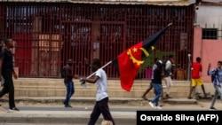 Manifestante carrega a bandeira angolana numa manifestação anti-governo em Luanda, 24 outubro 2020