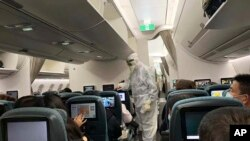 FILE - A worker in a hazardous materials suit takes the temperature of a passenger on a Cathay Pacific flight from Hong Kong to Rome after it landed at Rome Fiumicino Airport in Rome, Italy, Jan. 31, 2020.