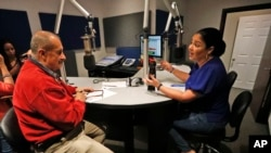 """In this Aug. 23, 2019 photo, Julio Cesar Camacho, a Venezuelan journalist and one of the most popular Spanish-language radio hosts, speaks with Democratic Florida Rep. Cindy Polo, during his show """"Democracia al Dia,"""" in Doral, Florida."""