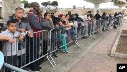 Những người tìm cách xin tị nạn tại Tijuana, Mexico, đang nghe gọi tên trong một danh sách chờ để đệ đơn xin tị nạn tại cửa khẩu ở San Diego, Mỹ (ảnh chụp ngày 26/9/2019)