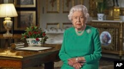 In this image taken from video and made available by Buckingham Palace, Britain's Queen Elizabeth II addresses the nation and the Commonwealth from Windsor Castle, Windsor, England, April 5, 2020.