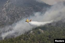 A firefighting plane from Spain drops water to a wildfire near Koycegiz, Turkey, Aug. 4, 2021.