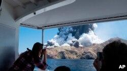 Foto oleh Michael Schade, tampak para turis mengabadikan letusan gunung berapi di White Island, Selandia Baru, 9 Desember 2019.
