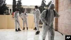 Members of a humanitarian aid agency disinfect Ibn Sina hospital as prevention against coronavirus in Idlib, Syria, March 19, 2020.