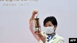 Tokyo Governor Yuriko Koike holds the Olympic flame during its unveiling ceremony at the Komazawa Olympic Park General Sports Ground, in Tokyo, July 9, 2021.