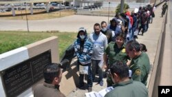 FILE - U.S. Border Patrol officers return a group of migrants back to the Mexico side of the border, as Mexican immigration officials check a list, in Nuevo Laredo, Mexico, July 25, 2019.