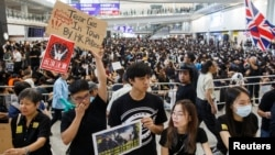 FILE - Anti-extradition bill protesters hold up placards for arriving travelers during a protest at the arrival hall of Hong Kong International Airport in Hong Kong, China, Aug. 9, 2019.