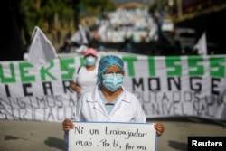 Un miembro del sindicato de trabajadores del ISSS sostiene una pancarta durante una protesta pidiendo medidas de cuarentena para contener la propagación de la enfermedad en El Salvador, 16 de julio 2020.
