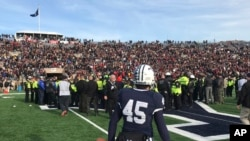 Yale punter Jack Bosman watches as demonstrators stage a protest on the field at the Yale Bowl, disrupting the start of the second half of a college football game between Harvard and Yale, Nov. 23, 2019, in New Haven, Conn.