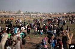 FILE - In this June 14, 2015 file photo taken from the Turkish side of the border between Turkey and Syria, in Akcakale, Sanliurfa province, southeastern Turkey, thousands of Syrian refugees walk in order to cross into Turkey.