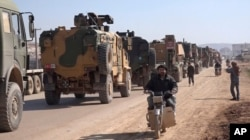In this frame grab from video taken Feb. 2, 2020, a large Turkish military convoy is seen at the northern town of Sarmada in Idlib province, Syria.