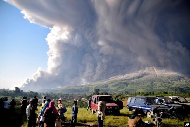 Warga menyaksikan Gunung Sinabung memuntahkan abu vulkanik saat meletus di Karo, Sumatera Utara, Selasa, 2 Maret 2021. (Foto: Ilustrasi/AP).