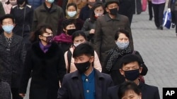 FILE - People wear face masks amid the concern over the spread of the coronavirus in Pyongyang, North Korea, April, 1, 2020.